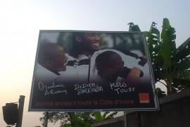 オレンジ・コートジボワールの新春広告。主役はサッカー・ コートジボワール代表だった左からアルーナ・ディンダネ、ディディエ・ドロバ(ドログバ)、 コロ・トゥーレ