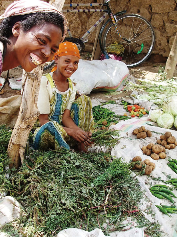 村の市場で、香草や香辛料、野菜を売る親子