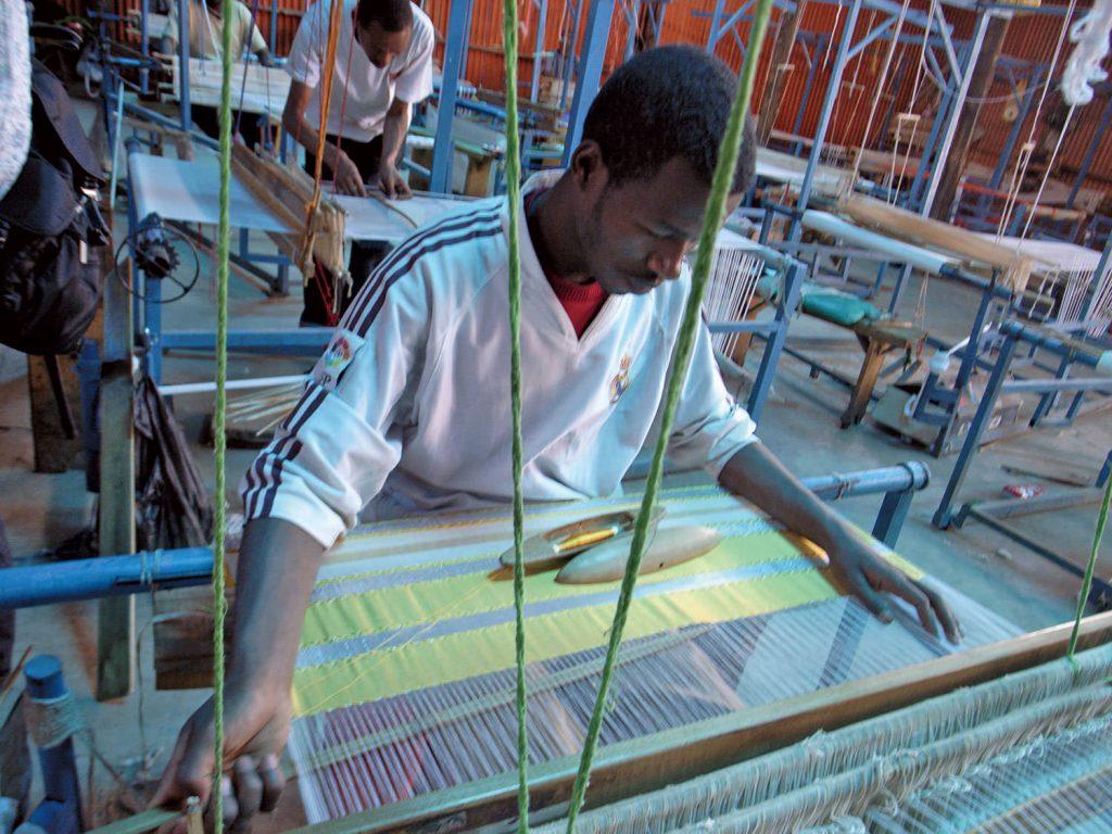 織り子は男性、糸紬は女性と分業で布が織られる