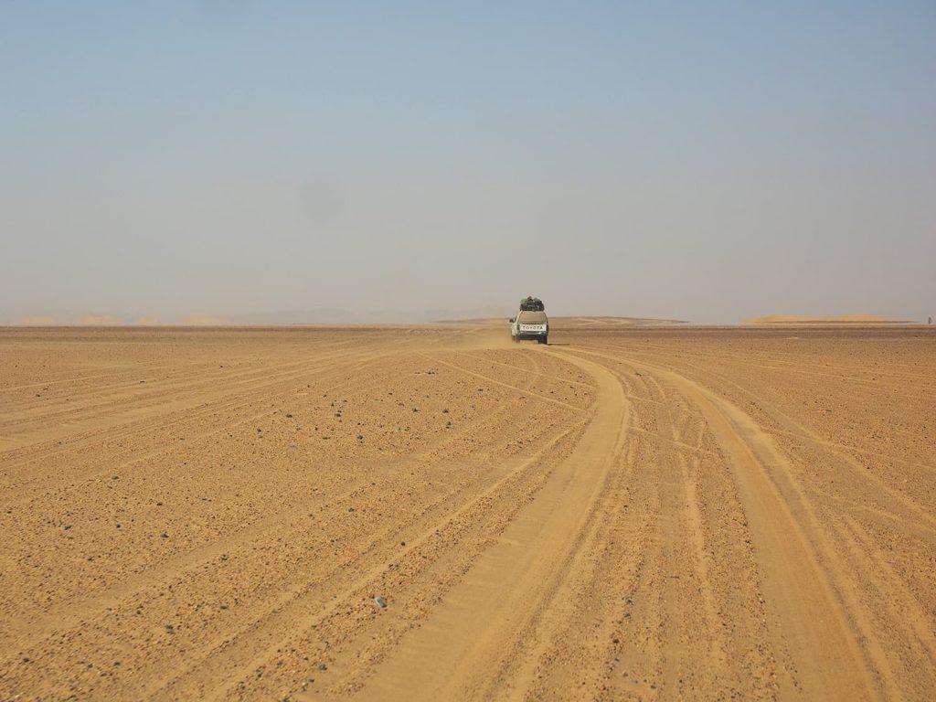 遠くに鉄分を含んだ黒い岩山を眺めつつ、真っ平な土漠を走ります。