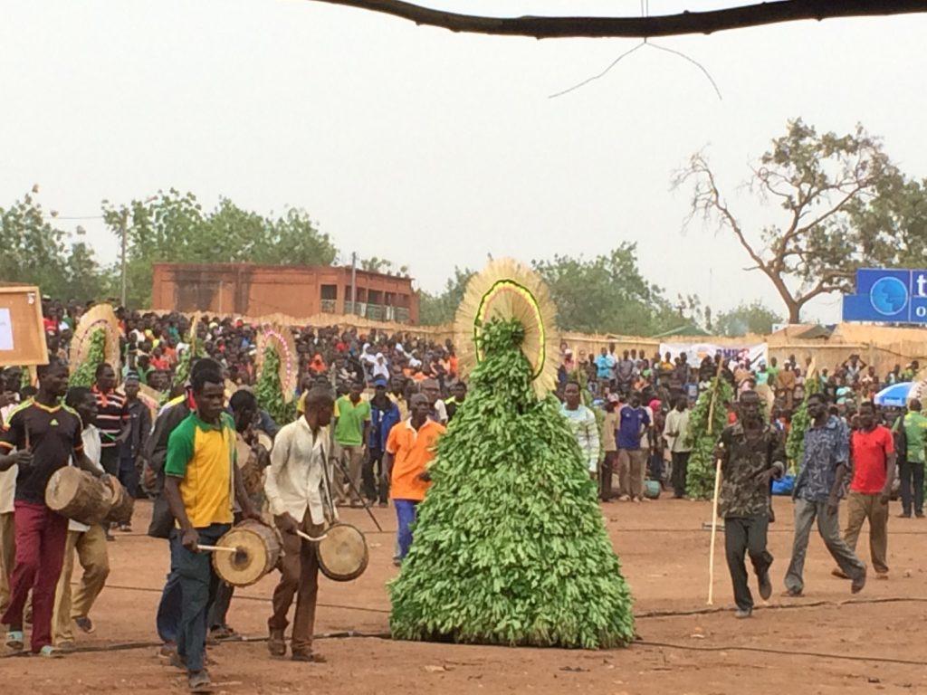 部族毎・村毎に参加者が会場を行進。真ん中の植物は置物?いいえ、くるくる回って踊れるんです!