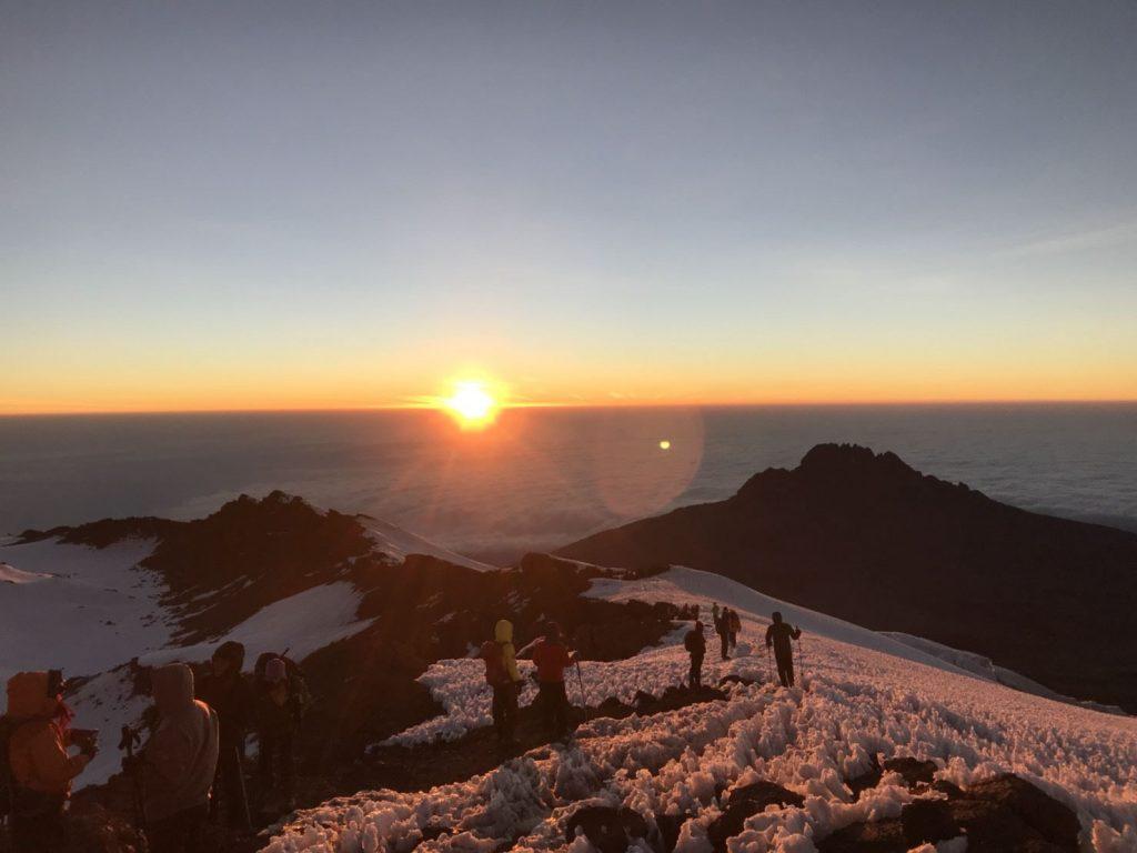 マウェンジ峰の向こうの雲海から昇ってくる朝日