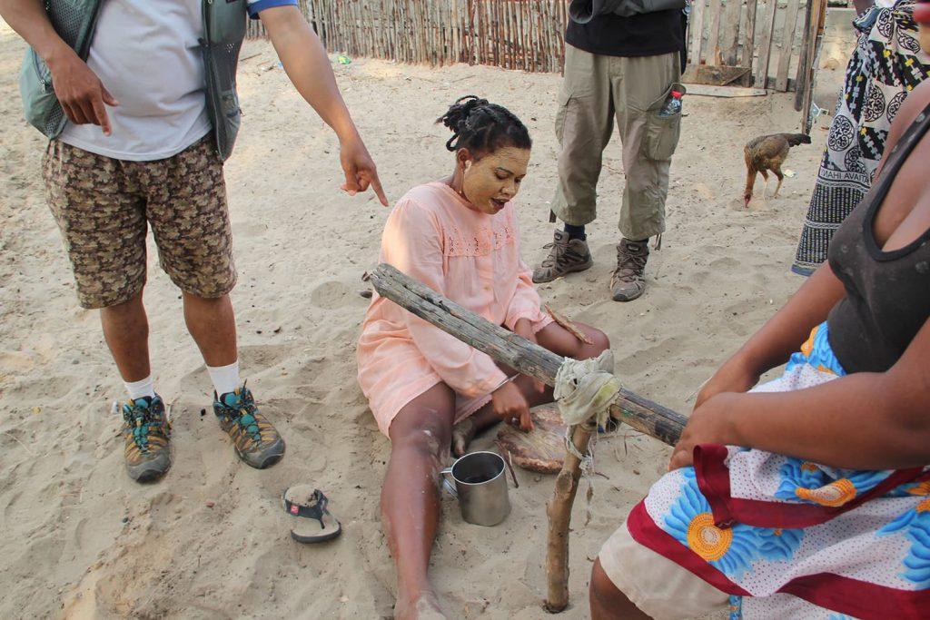 村散策中、マダガスカル女性が日焼け止めと美容のために顔に塗っている「タバキ」をご参加者も体験!