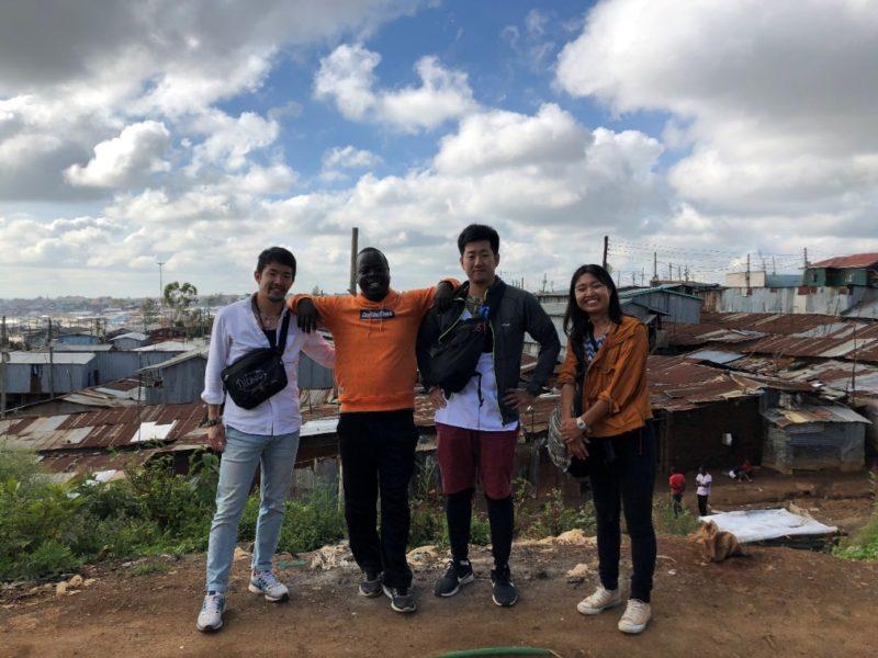 キベラの拓けた写真スポット。マゴソスクールのオギラ先生と道祖神 根本さんと。後ろに見えるバラックですが、最近は人が増えすぎて平屋ではなく2階建てのバラックが増えてきているとの事。