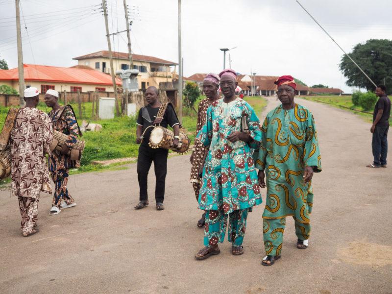 ドラムの音で出迎えられたのは地元の有力者たち。仕立てた布地を着こなしています。
