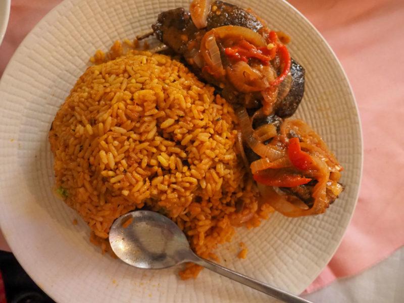 次は国民食「ジョロフライス」ピリ辛チャーハンです。これは日本人の口にもよく合います。セネガルのジョロフ王国の料理「チェブジェン」がルーツと言われています。一緒に食べているおかずは、ちょっと分かりにくいですがカタツムリ。エスカルゴ(大)です。