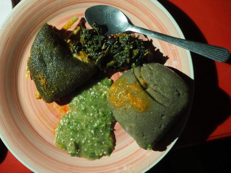 これぞナイジェリア料理。黒っぽいのは「アマラ」です。見た目は「フフ」に似ていますが、乾燥したキャッサバ芋から造るのが特徴。ちょっと発行しているので酸味があります。クセになる味。付け合わせの野菜は「エフォリロ」。ヨルバの人々の伝統料理で、ほうれん草のようなEfinrinという葉とEfo sokoという葉を、スパイスで炒めます。おかずは牛の腸壁。モツ焼きですね。