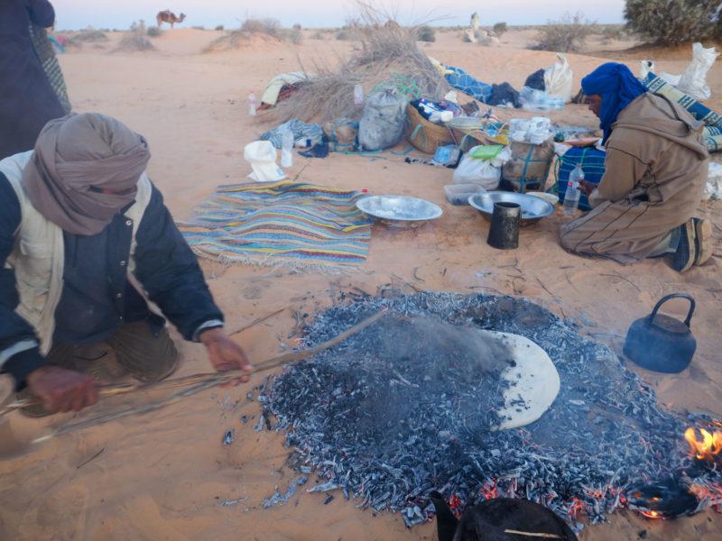 そして焚火をした後の砂地の上に直接置き、焚火の灰を上から被せていきます。