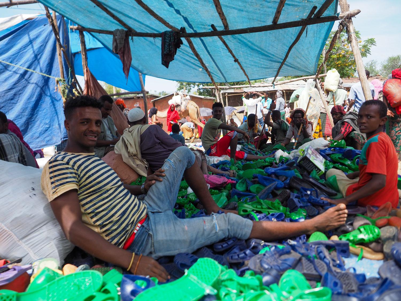 中国製のサンダルを売る兄ちゃんたち。日常生活品は中国製のものが増えています。